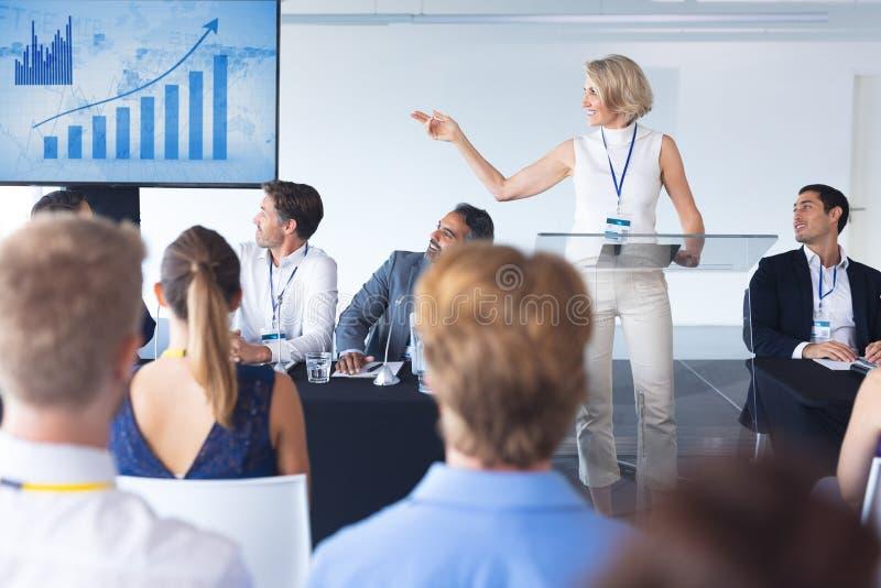Samica mówiąca pokazująca na ekranie wykres biznesowy w seminarium biznesowym zdjęcia stock