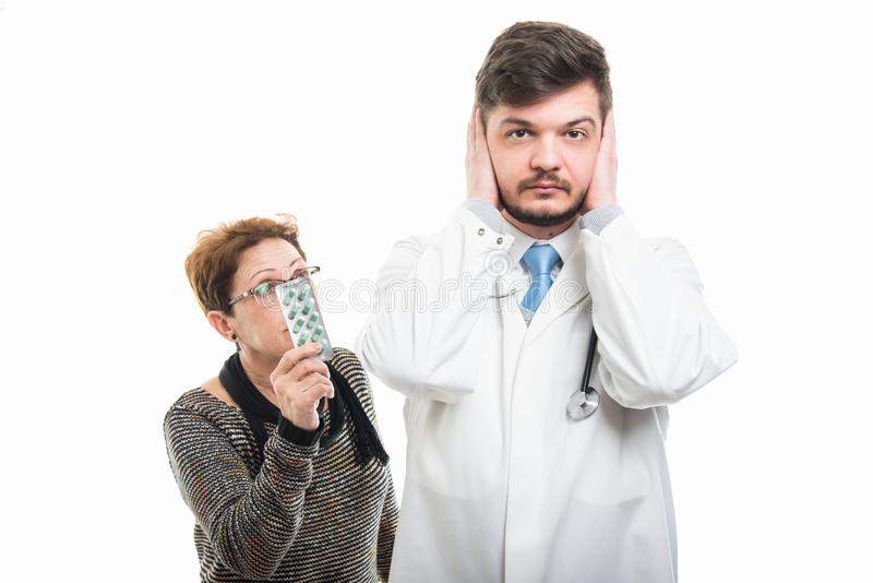 Samiec doktorscy nakrywkowi ucho i żeński pacjent pokazuje pigułki zdjęcia stock