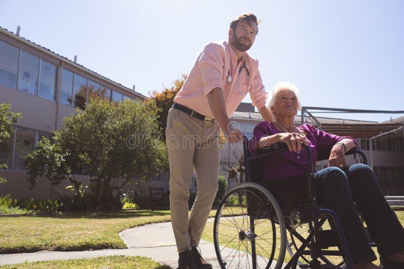 Samiec doktorska czułość obezwładniał starsze cierpliwe kobiety w wózku inwalidzkim obraz royalty free