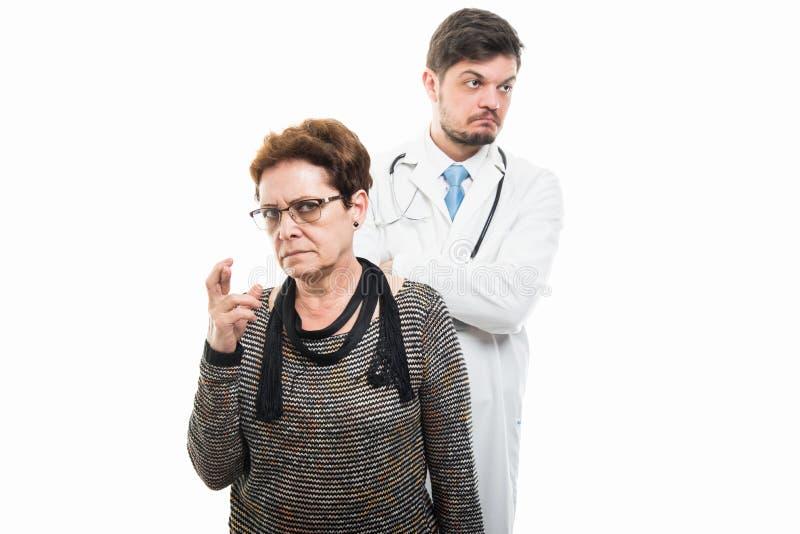 Samiec doktorska i żeńscy starsi cierpliwi mienie palce krzyżujący obrazy stock