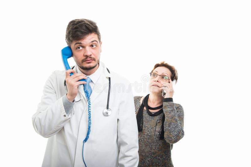 Samiec doktorska i żeński starszy pacjent opowiada przy telefonami zdjęcia royalty free