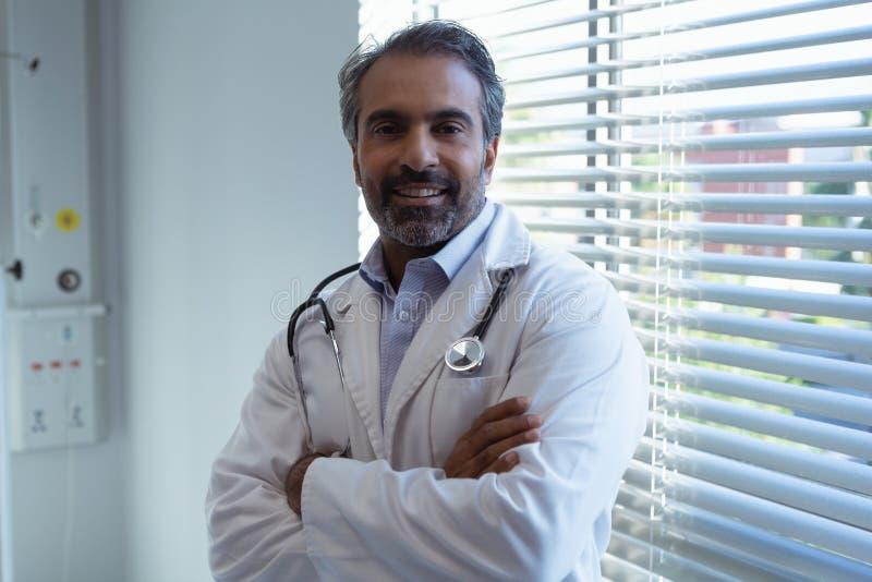 Samiec doktorska pozycja z ręką krzyżującą i patrzeje kamerę w klinice przy szpitalem zdjęcia royalty free