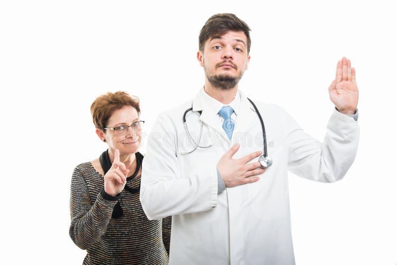 Samiec doktorski i żeński starszy cierpliwy pokazuje ślubowanie gest obraz royalty free