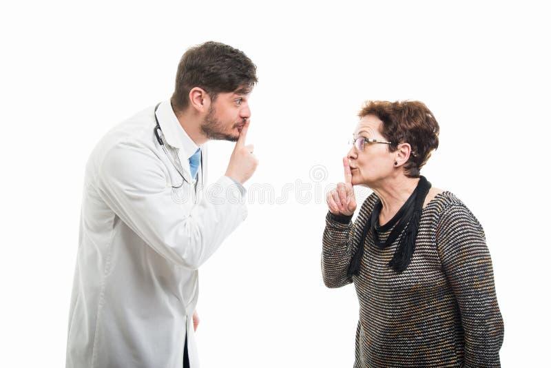 Samiec doktorski i żeński starszy pacjent oba pokazywać cichy obrazy stock