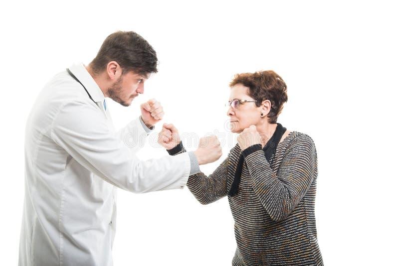 Samiec doktorski i starszy żeński cierpliwy bój z pięściami obraz royalty free