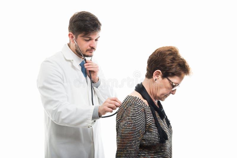 Samiec doktorski ordynacyjny żeński starszy pacjent z stetoskopem zdjęcia royalty free