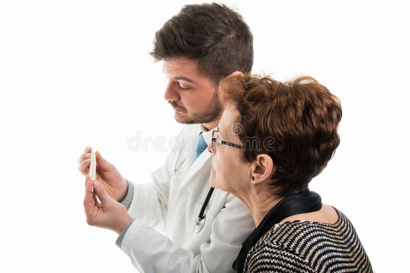 Samiec doktorski pokazuje termometr żeński starszy pacjent fotografia stock