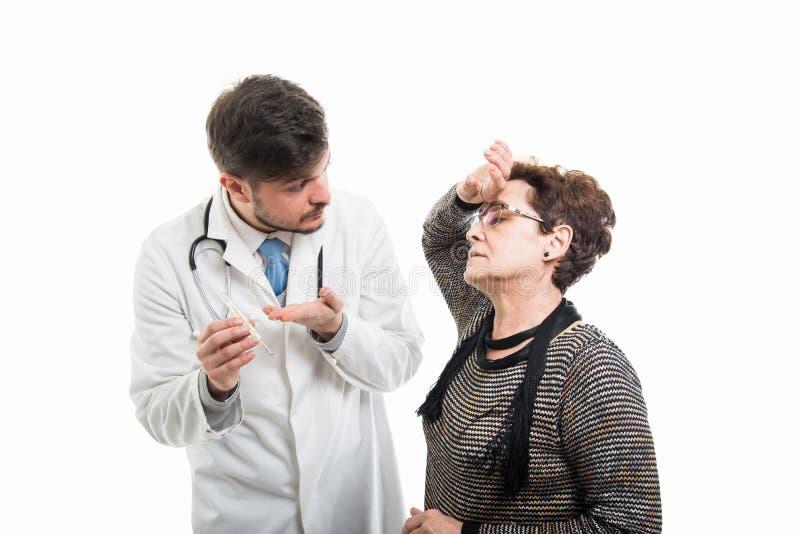 Samiec doktorski pokazuje termometr żeński starszy pacjent obrazy stock