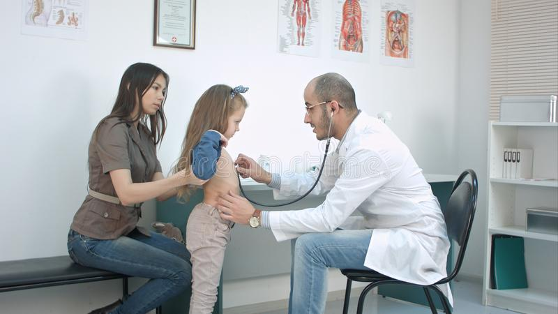 Samiec doktorski słuchanie dziewczyny klatka piersiowa z stetoskopem w jego biurze obraz royalty free