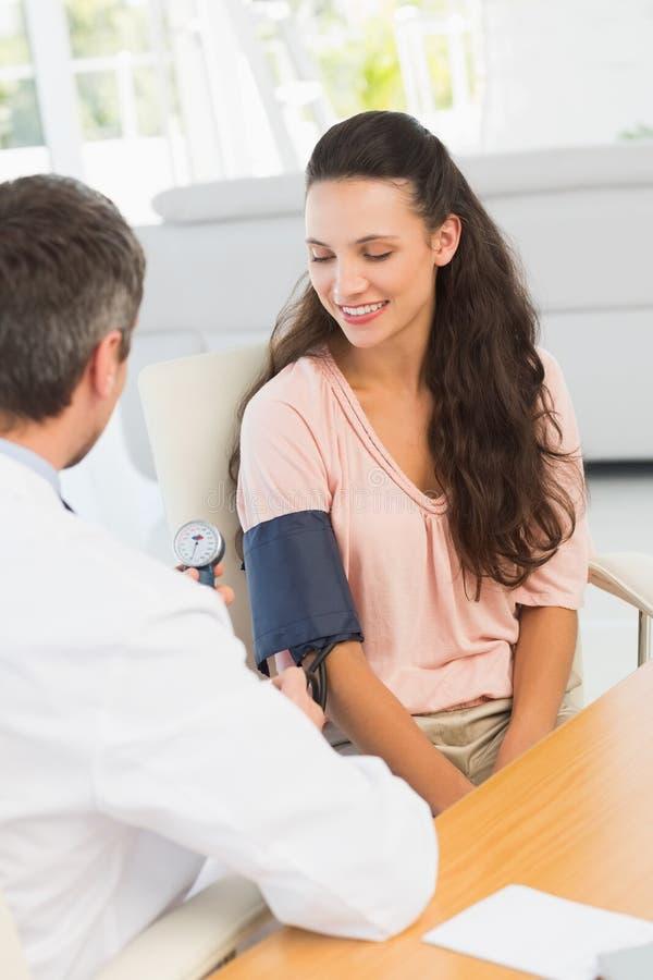 Samiec doktorski sprawdza ciśnienie krwi młoda kobieta zdjęcia stock