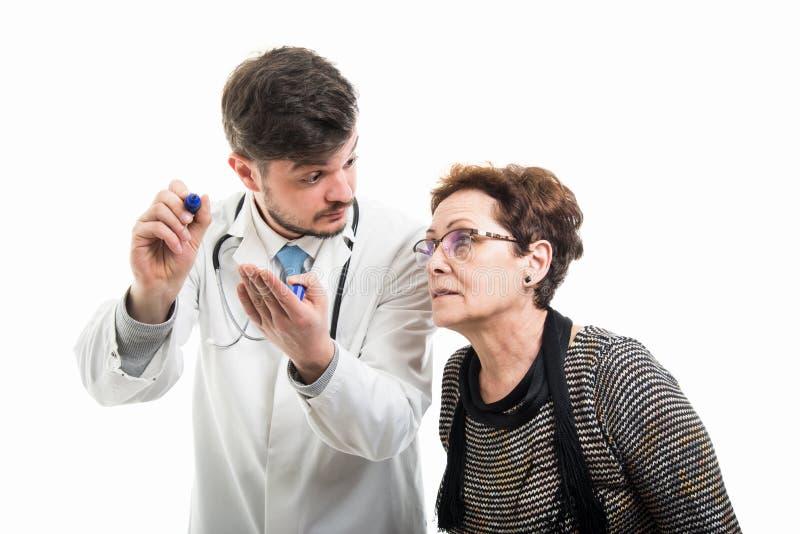 Samiec doktorski wskazywać żeński starszy pacjent z błękitnym markierem zdjęcie royalty free