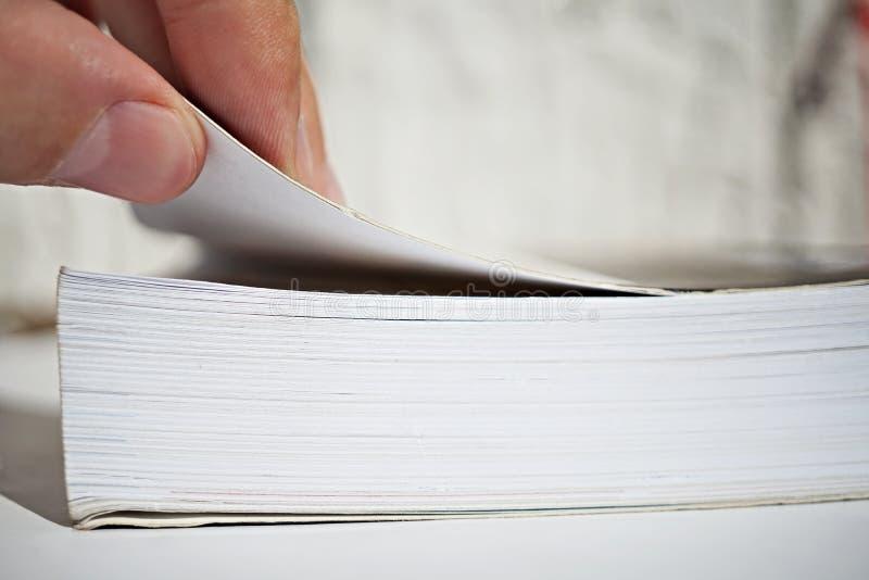 Samiec dotyka kręcenia otwarcie i strony jako symbol czytanie gęsta książka lub zyskiwać wiedza i informacja zdjęcia royalty free