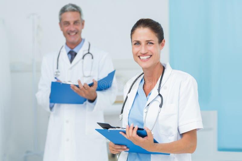 Samiec i kobiety lekarki pracuje na raportach fotografia royalty free