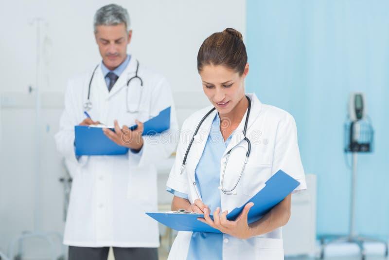 Samiec i kobiety lekarki pracuje na raportach obraz royalty free