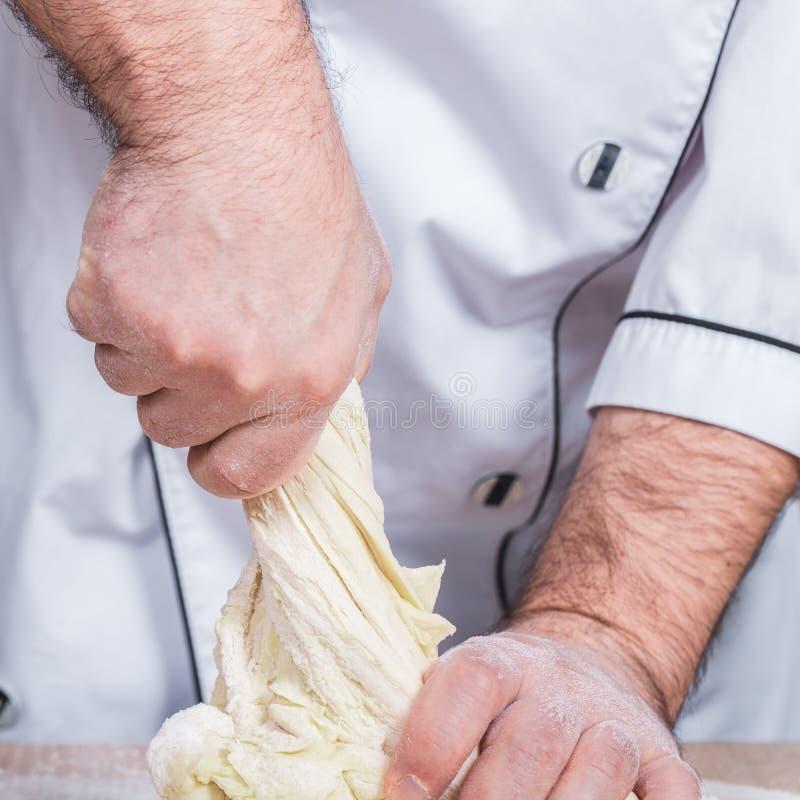 Samiec kucharz ugniata ciasto na stole obraz stock