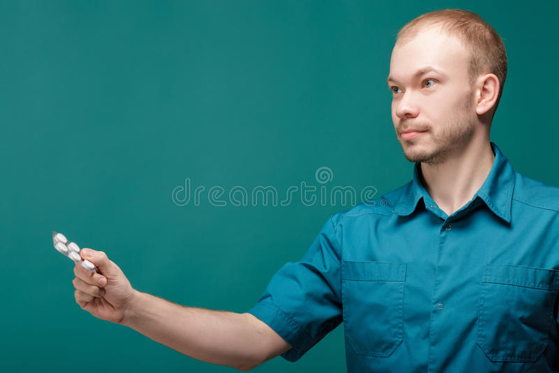 Samiec lekarka daje pigułce na błękitnym tle zdjęcia royalty free