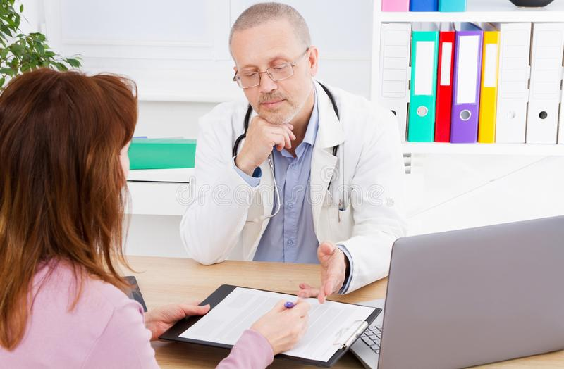 Samiec lekarka dyskutuje kontrakt z jego pacjentem w medycznym biurze zdjęcie stock