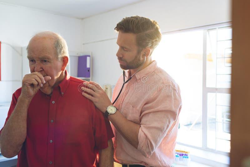 Samiec lekarka egzamininuje seniora cierpliwych dzięki stetoskop obrazy stock