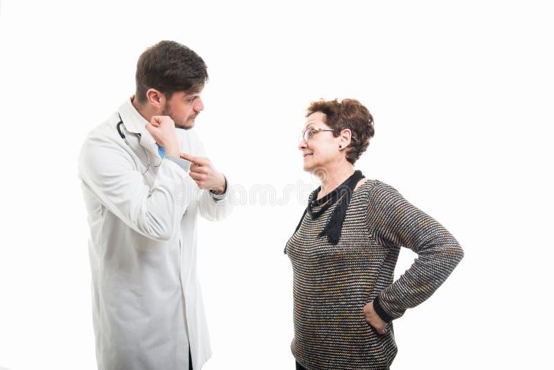Samiec lekarka pokazuje opóźnionego gest żeński starszy pacjent fotografia stock