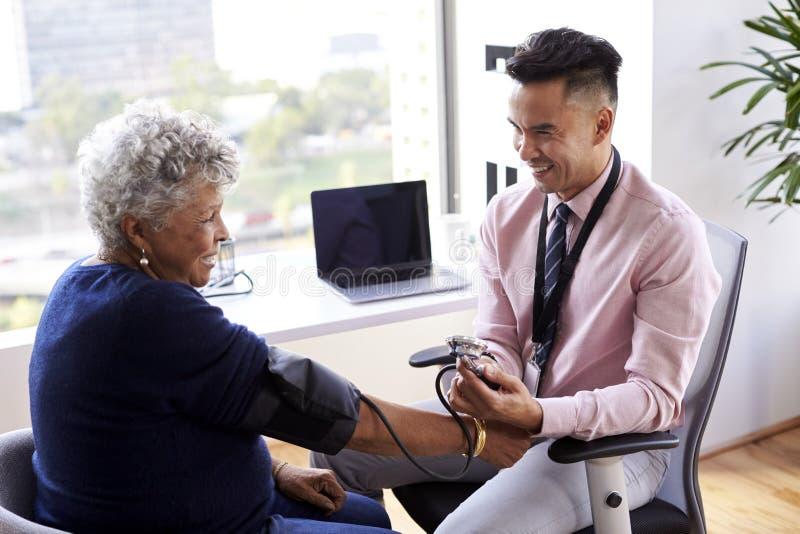 Samiec lekarka Sprawdza Starszego Żeńskiego pacjenta ciśnienie krwi W biurze zdjęcia stock