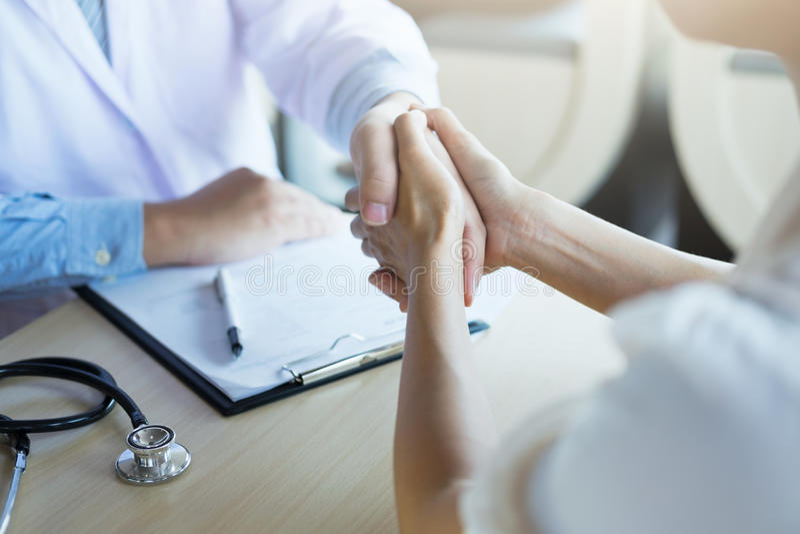 Samiec lekarka w białej żakieta chwiania ręce żeński kolega zdjęcie royalty free