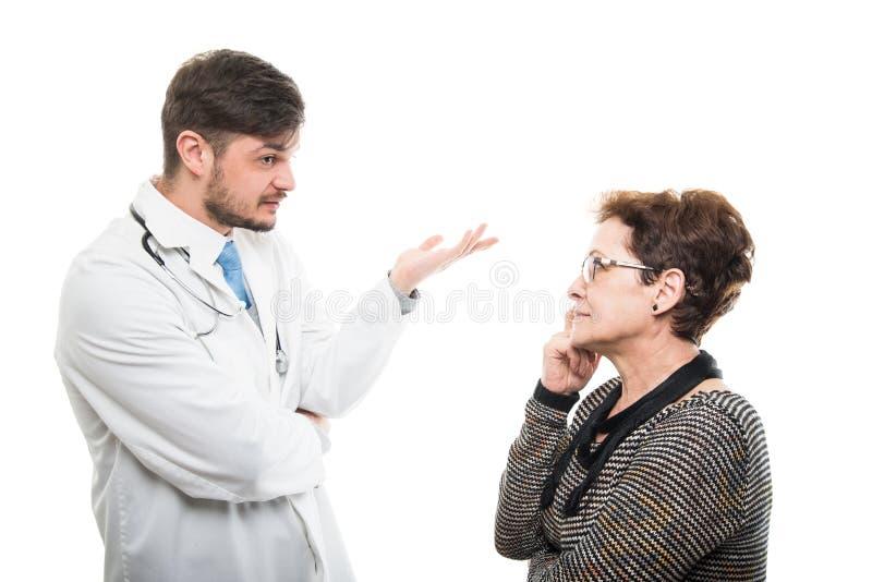 Samiec lekarka wyjaśnia coś starszy żeński pacjent zdjęcia stock