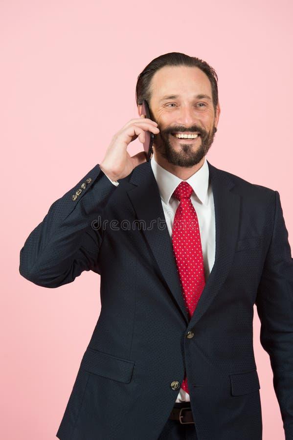 Samiec mówi nad telefonem odizolowywającym w studiu z różowym tłem Mężczyzna w zmroku - błękitni kostiumów uśmiechy gdy opowiadaj zdjęcie stock