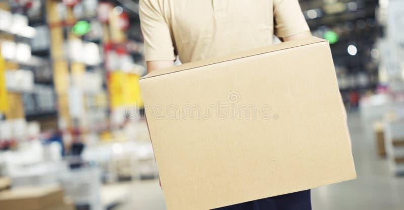 Samiec magazynowy pracownik niesie kartonu pudełko zdjęcia stock