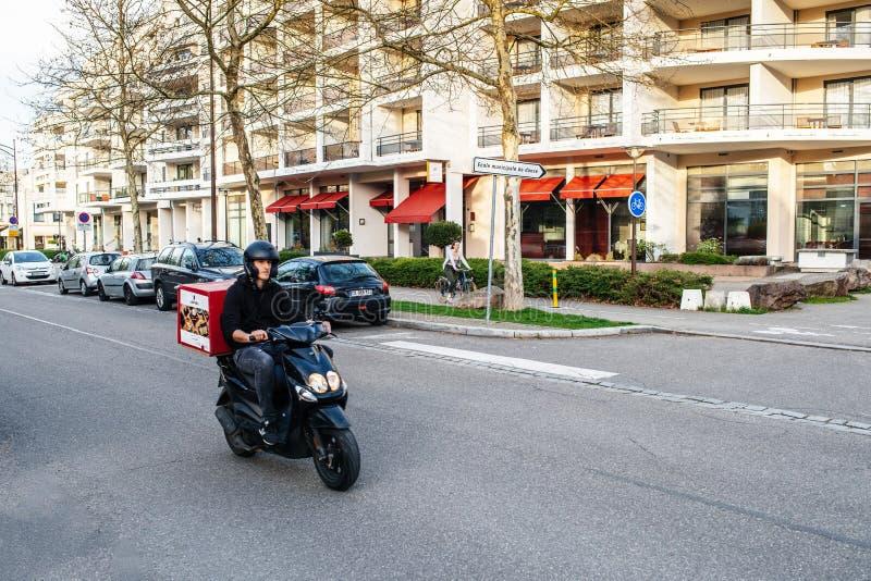 Samiec na hulajnodze na ulicach dostarcza suszi Strasburg fotografia stock