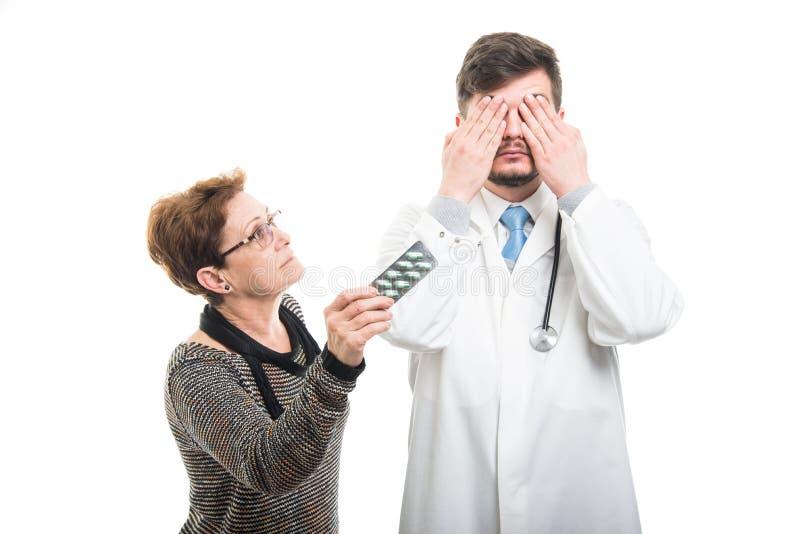 Samiec nakrycia doktorscy oczy i żeński pacjent pokazuje pigułki obraz royalty free