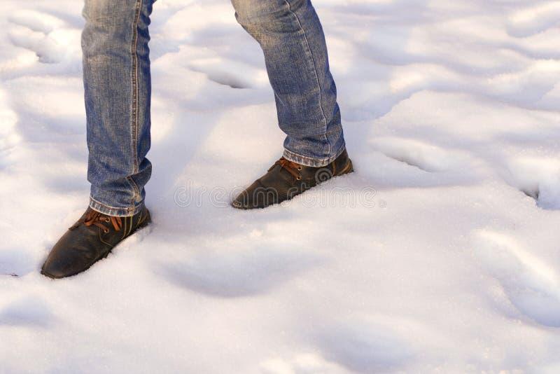 Samiec nogi w brązów niebieskich dżinsach i butach iść na śniegu kosmos kopii Wirst krok po śnieżnej katastrofy zdjęcia stock