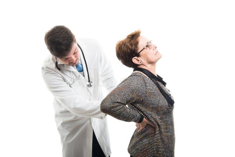 Samiec pacjenta doktorski sprawdza żeński starszy plecy obraz royalty free