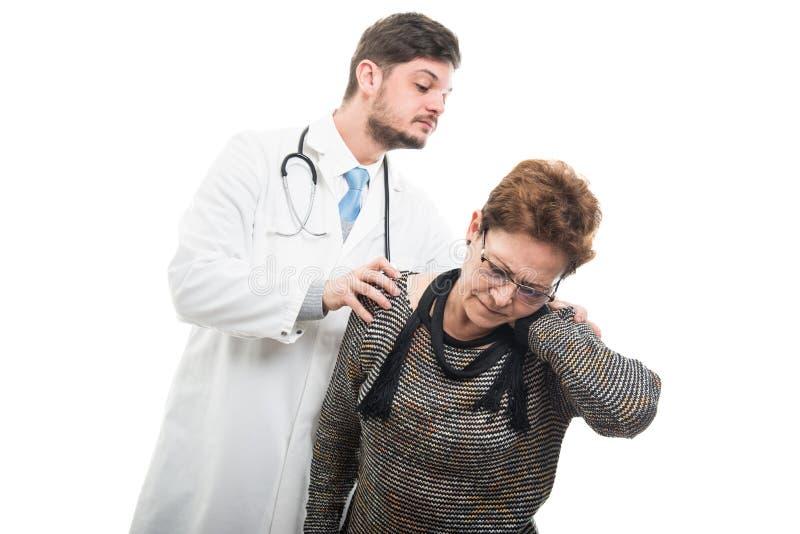 Samiec pacjenta doktorski sprawdza żeński starszy ramię obrazy stock
