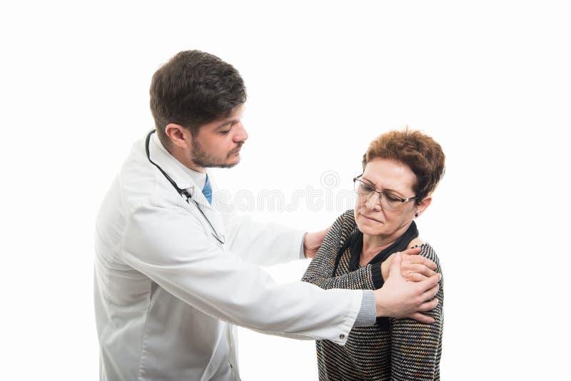 Samiec pacjenta doktorski sprawdza żeński starszy ramię obrazy royalty free