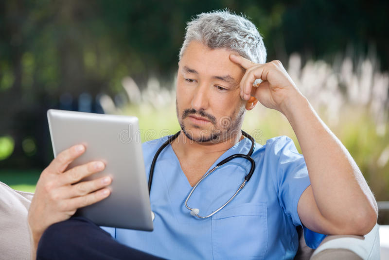 Samiec pastylki doktorski używa komputer osobisty zdjęcia stock