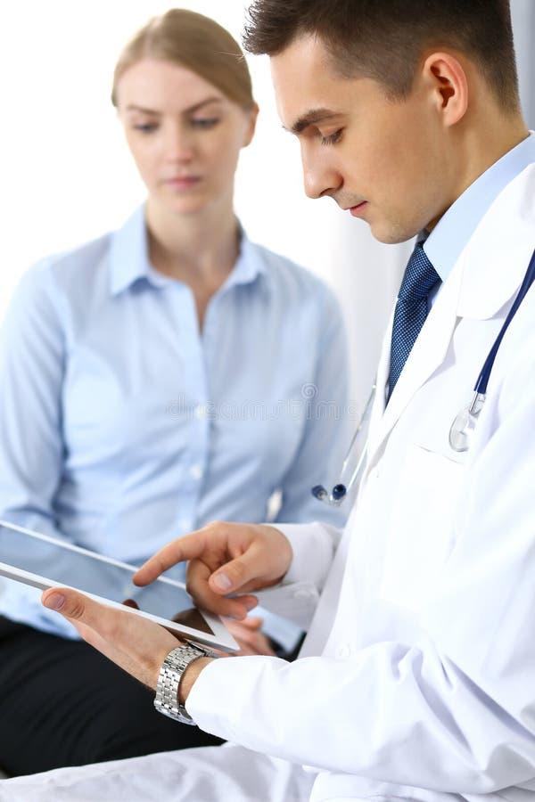 Samiec pastylki lub touchpad doktorski używa komputer osobisty podczas gdy konsultujący żeńskiego pacjenta w szpitalnym biurze Me obraz royalty free
