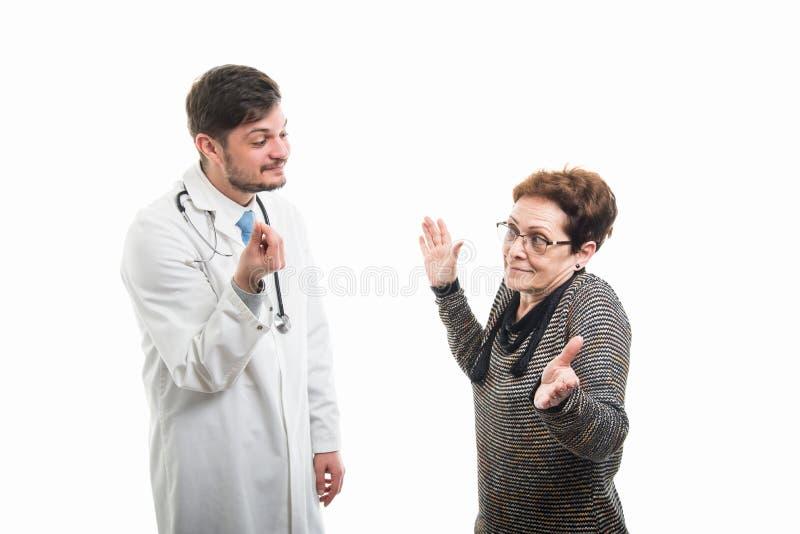 Samiec pieniądze doktorski robi gest żeński starszy pacjent zdjęcie royalty free