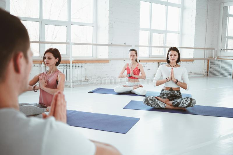 Samiec praktyki joga powozowy ćwiczenie z kobiety grupy salowym gym Wpólnie dostosowywający szkolenie Kobiety opieka zdrowotna po zdjęcie stock
