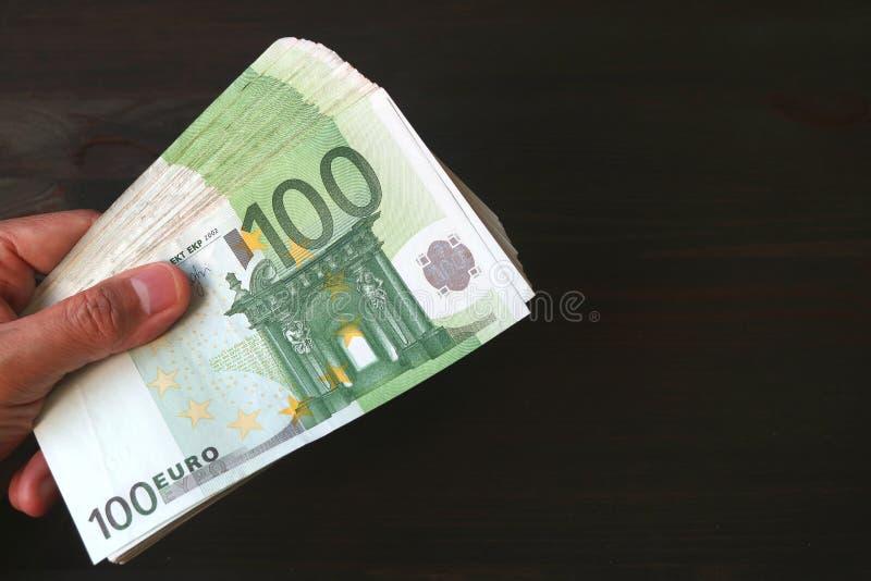 Samiec ręka Trzyma wiązkę 100 EURO banknotów na Czarnym tle zdjęcie royalty free