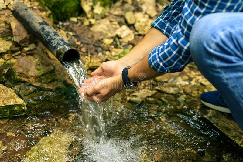 Samiec ręki pisać na maszynie w jej rękach czyścą wiosny wodę obraz stock
