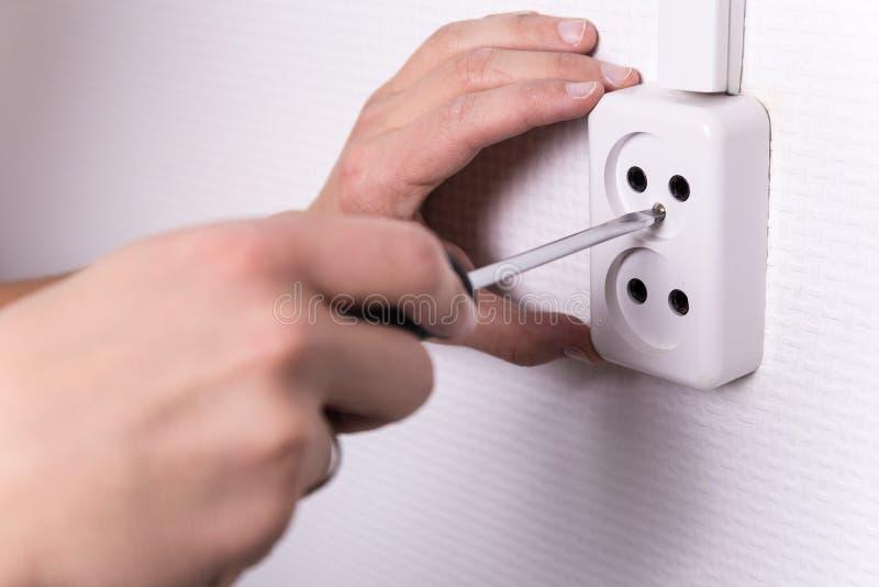 Samiec ręki z śrubokrętem instaluje elektryczną nasadkę na ścianie obraz royalty free