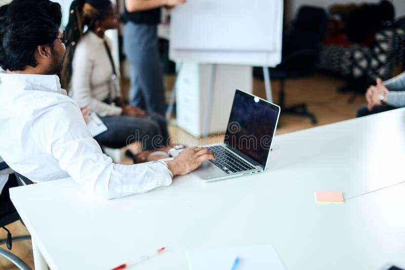 Samiec siedzi przy laptopem podczas gdy konferencja fotografia royalty free