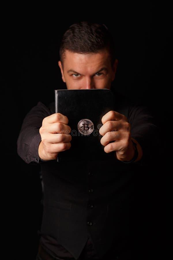 Samiec trzyma książkę z Bitcoin logem zdjęcia royalty free
