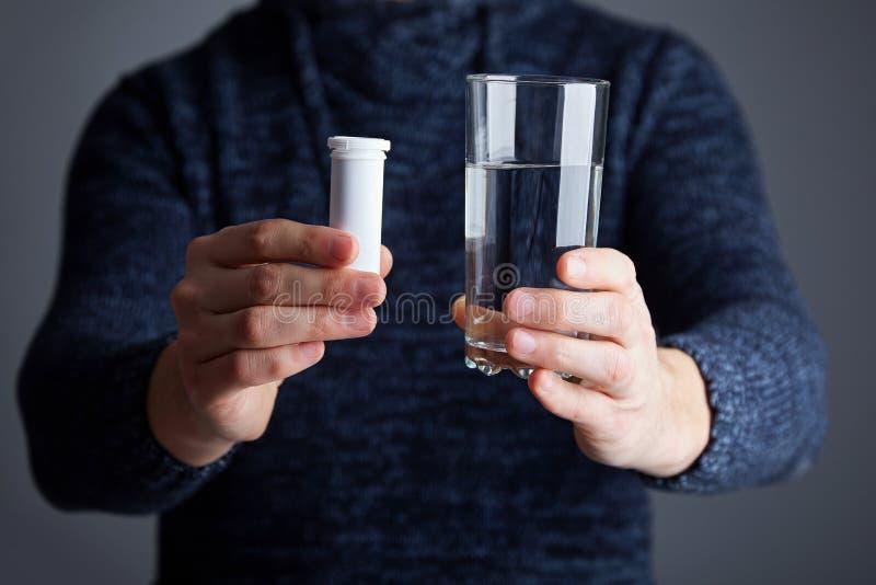 Samiec trzyma pigułki gotowe rozpuszczać jeden w wodzie zdjęcie stock