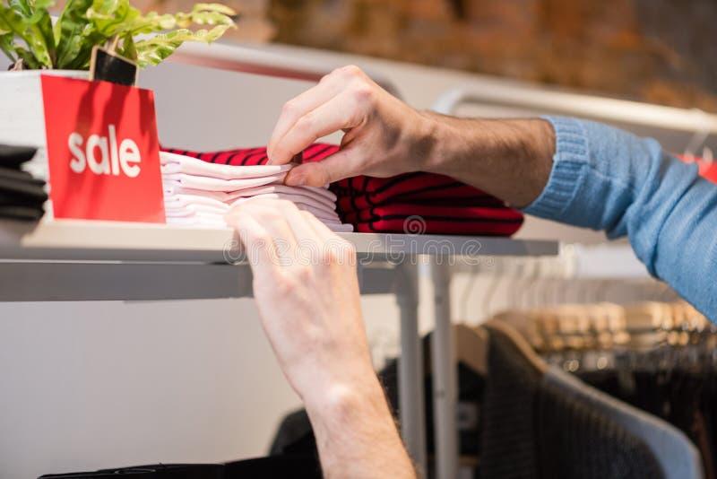 Samiec układa białe koszula i odzieżowego sklepu stojaka zdjęcie stock