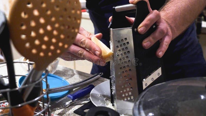 Samiec wręcza drażniącego ser na ruchliwie kuchennym stole - gotować, jedzenie i domowy pojęcie, zdjęcia stock