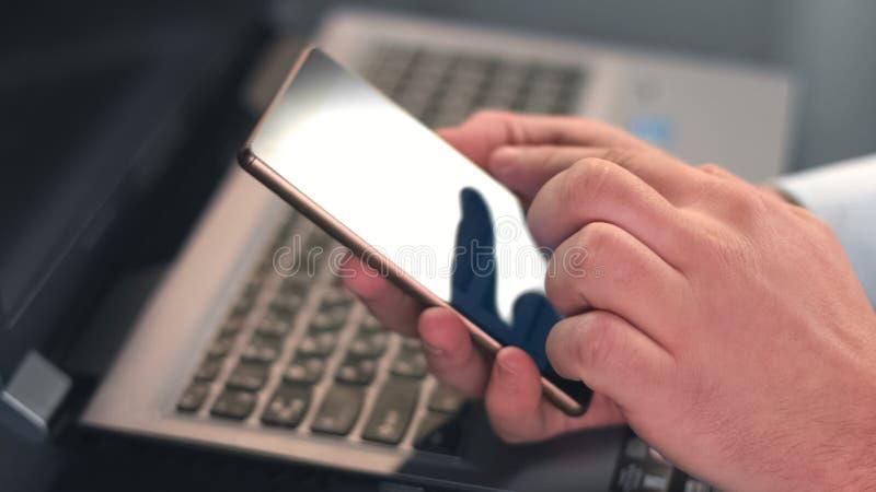Samiec wręcza pisać na maszynie wiadomość na smartphone zbliżeniu, scrolling fotografie, biznesowy app zdjęcie royalty free
