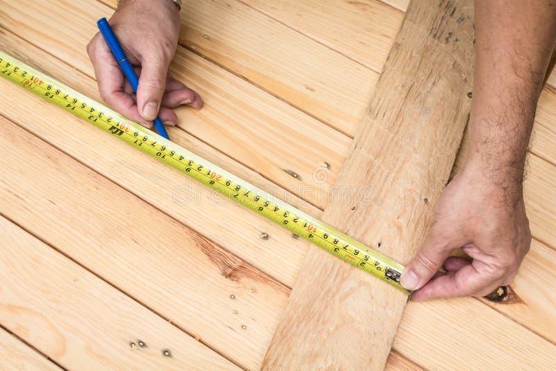 Samiec wręcza pomiarową drewnianą podłoga zdjęcie royalty free