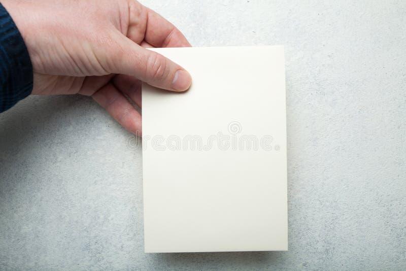 Samiec wręcza trzymać pustej ulotki na rocznika bielu tle Ulotka, zaproszenie w górę ilustracja wektor