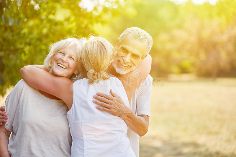 Samiling senior citizens greet each other with joy. In summer stock images